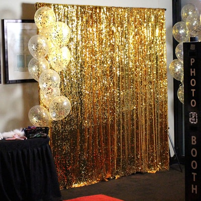 A gold background to take pictures in front of. A table with photo props set up to the left.