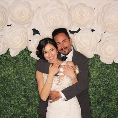 A wedding couple takes a picture in front of an open air photo booth with green and white flowers in Dallas.